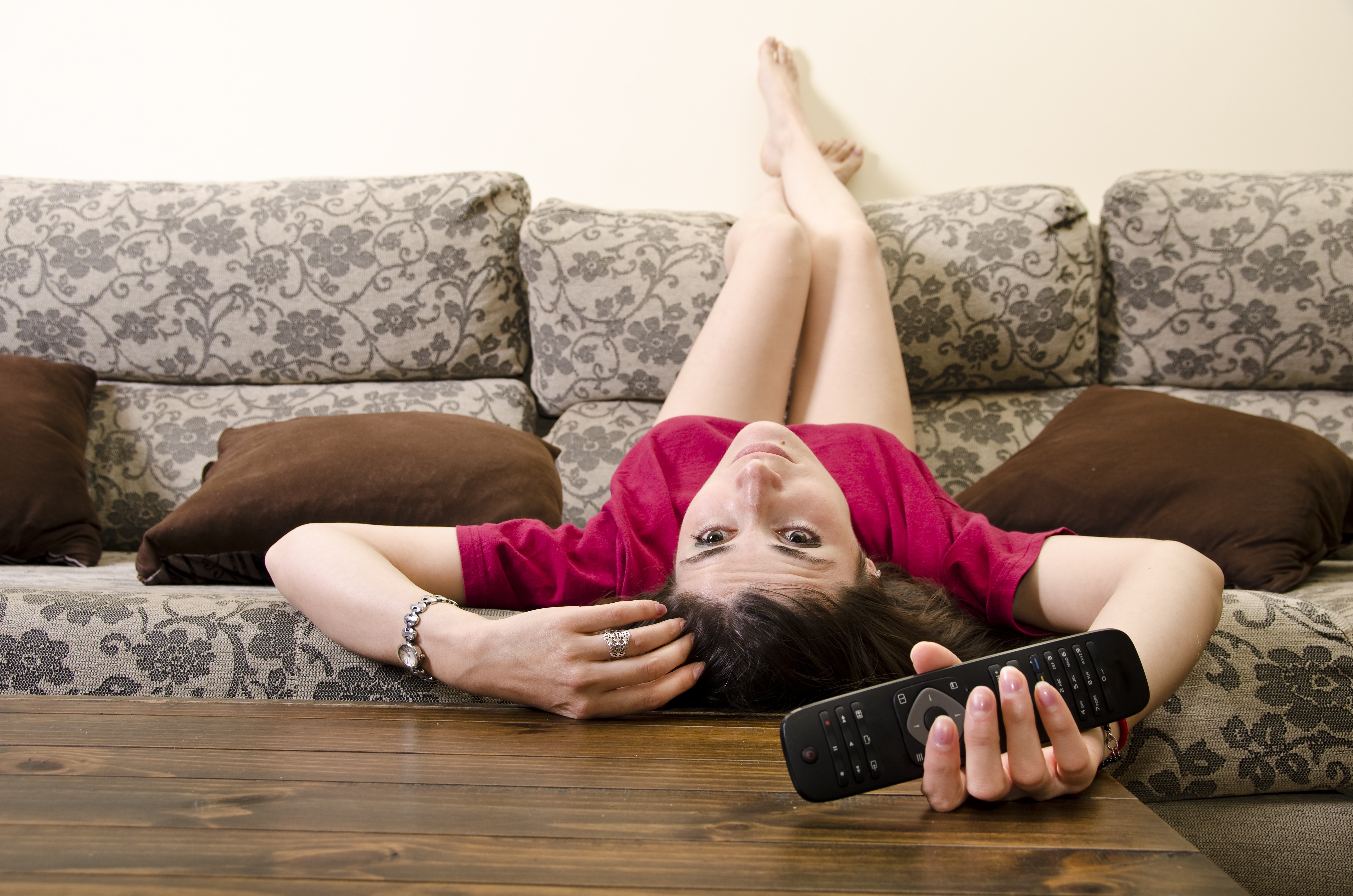 Girl lying facedown watching television alone.