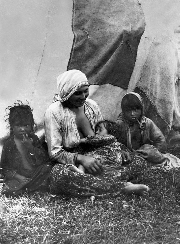 The photo form the 1930s shows a Roma woman breastfeeding a child. In the grass near her are two other children. Date: